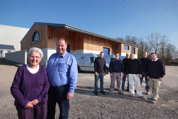 Managing Director, Neil Albury pictured with his mother, Mavis Albury with the new offices and members of the Gloweth team in the background.