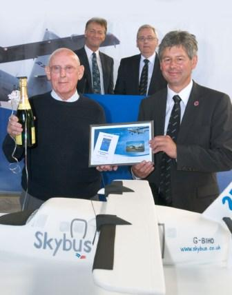 First ticketed passenger Alan Sibley receives certificate from Chairman of Isles of Scilly Steamship Company Andrew May. Andrew George MP, and Jeff Marston - Skybus Chief Exec (both in background)