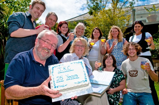 The John Knowles Company celebrate 25 years marketing in Cornwall with cake and champagne.