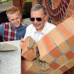 Kyle Ainsley and Dave Linnell lay the final brick
