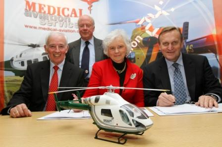 (l-r): Ian Brackenbury (Trustee)  Lady Mary Holborow (Chairman) Henk Schaeken (MD MAS) with Andrew Bell (Vice Chairman) standing, sign the contract that will see two new air ambulances serving Cornwall from December 2014