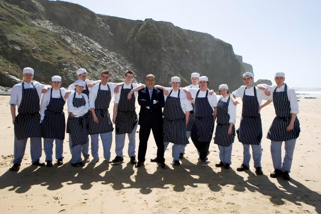 Fifteen Cornwall Cohort 7 graduates on the beach at Watergate Bay with Genaro Contaldo