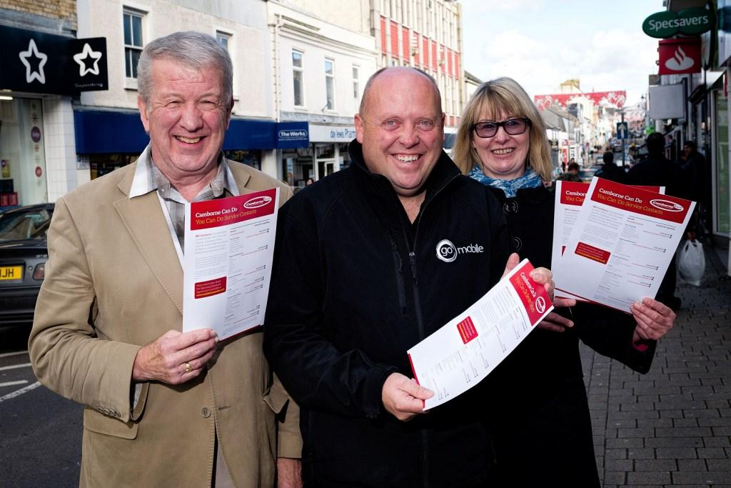 BID Camborne chairman George Le Hunte (l) and BID Manager - Mel Martin (r) present the You Can Do sheet to Ian Gilbert from Go Mobile