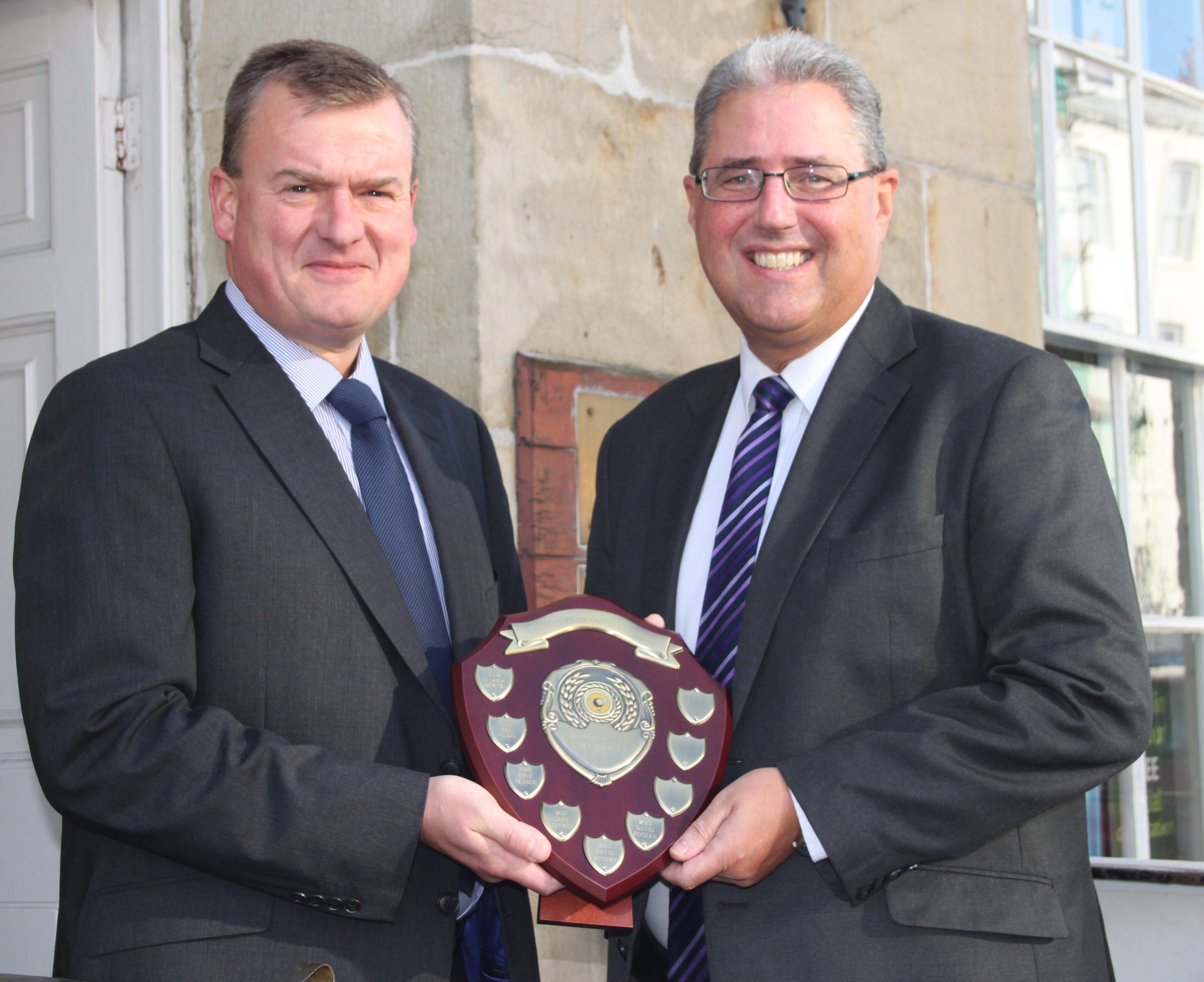 Worldwide Financial Planning's Matt Higham (l) presents the Worldwide Financial Planning Professional Services Golf League trophy to David Rogers.