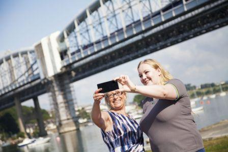 Sheryll Murray MP for South East Cornwall an EE Store Manager, Emily Lane, celebrate the launch of 4G in Saltash under the Royal Albert Bridge