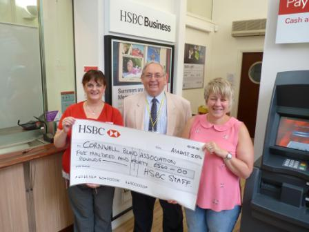 Jill Colton (l) and Sharon Waters(r ) present a cheque to Charles Whitehead from The Cornwall Blind Association
