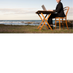 Woman with desk by the sea